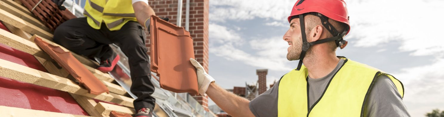 Urban roofers passing on roof tile towards colleague working on the roof wearing safety jackets and hard hats
